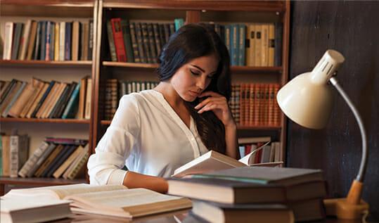 Girl reading a book at a desk.