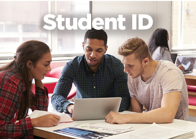 3 students sitting at a table looking at a laptop. Photo says Student ID